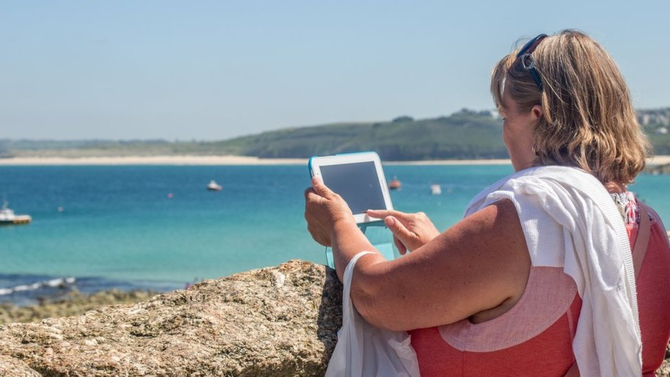 File photo of a woman on a beach with a tablet
