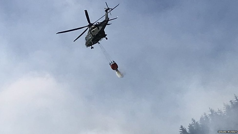 Helicopter dropping water over fire