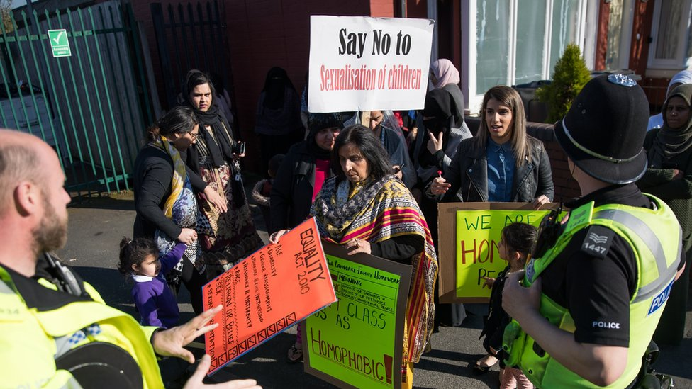"Police and parents at a protest outside a school. A placard reads ""Say no to sexualisation of children"""