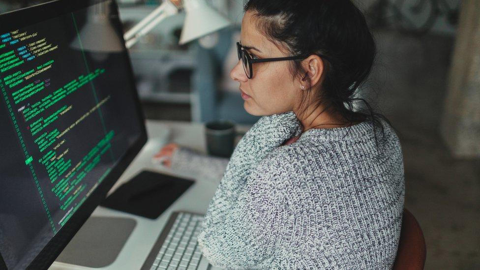 Mujer frente a una computadora manejando lenguaje de código para web.