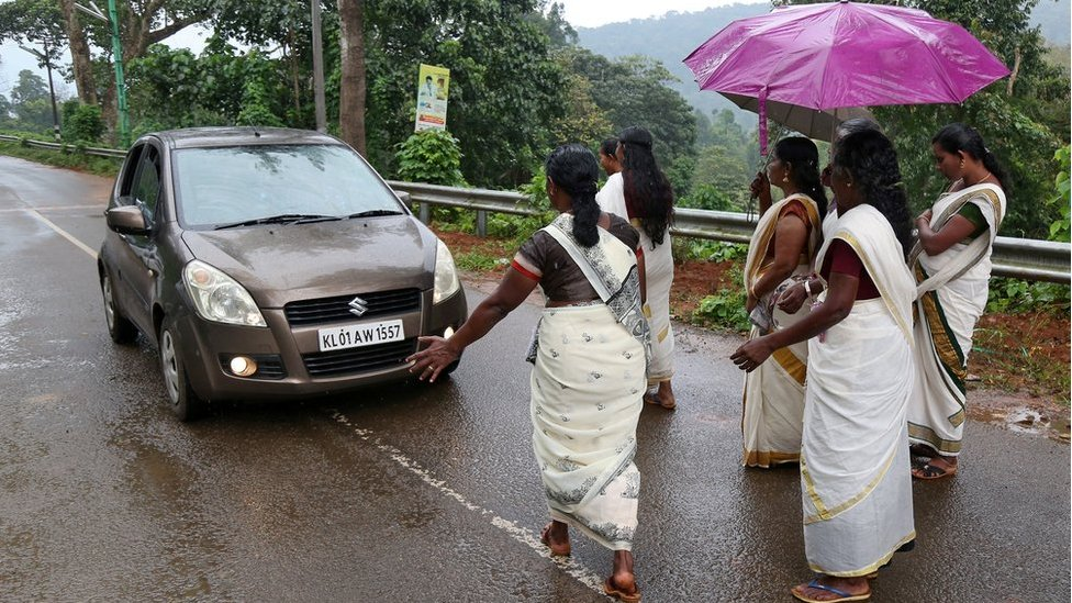 Hindu devotees stop a car to check if any women of menstruating age are headed towards the Sabarimala temple.