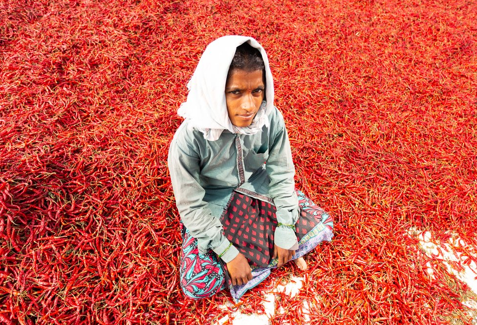 A girl sits on the ground covered in red chillies