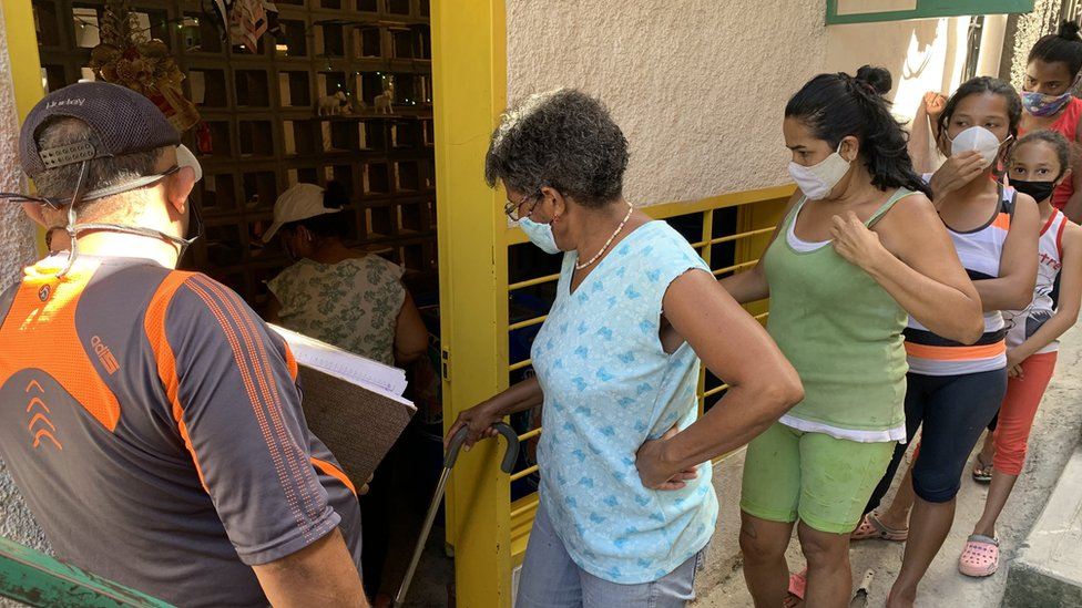 People queue at a soup kitchen in Catia
