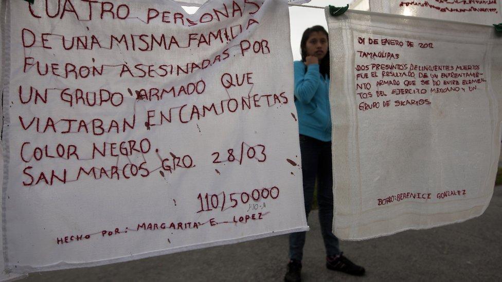 Mujer con mantas en las que se leen mensajes sobre desapariciones y nombres de desaparecidos durante una protesta en Monterrey.