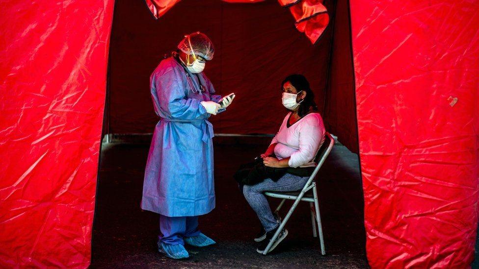 Enfermera tomando una prueba de covid-19 a una mujer en Perú.