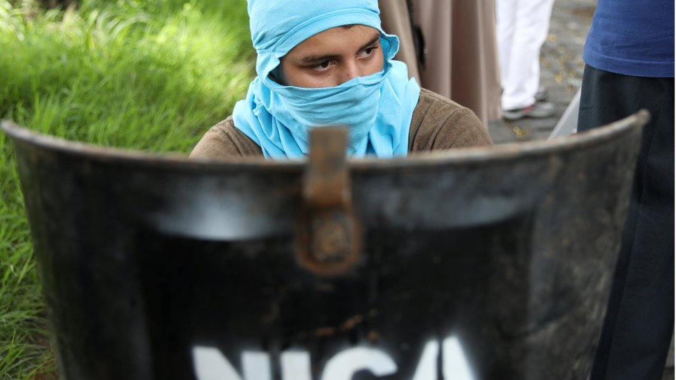 A protestor sits behind a homemade shield next to National University of Nicaragua (UNAN) after clashes in Managua, Nicaragua, June 23, 2018.