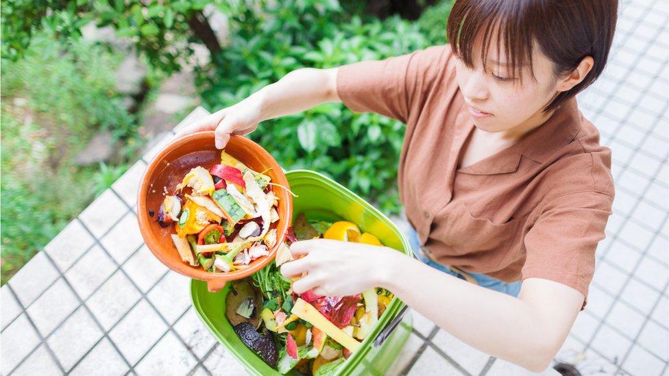 žena baca hranu u kompost