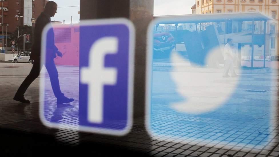 Facebook and Twitter logos on a shop window in Malaga, Spain, 4 June 2018