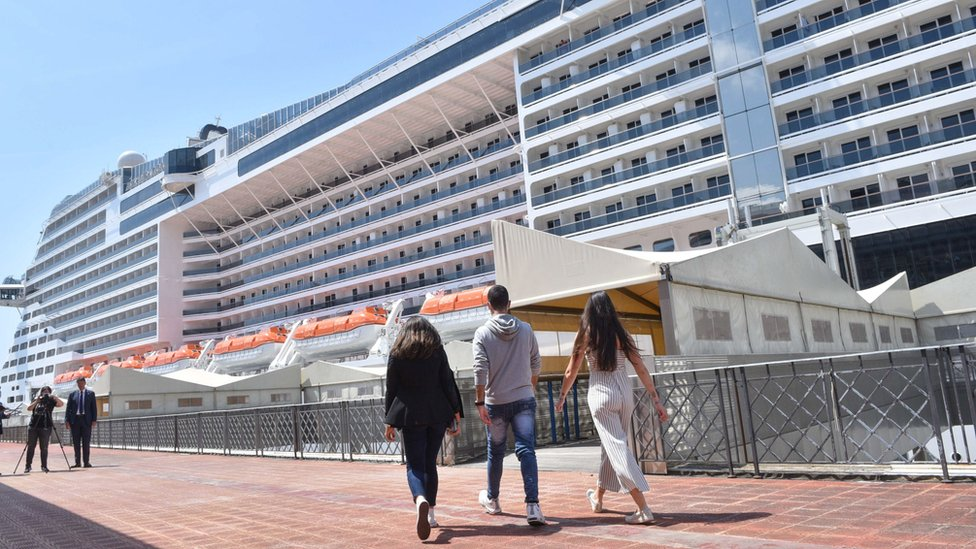 People on their way to board the MSC Grandiosa cruise ship at a port in Genoa, northern Italy
