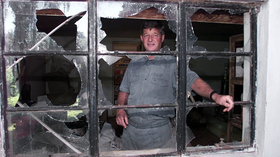 Paul Retzlaff in front of a broken window at his home in Arcturus, 30km east of Zimbabwe's capital, Harare, a day after clashes broke out at his farm - 12 April 2000