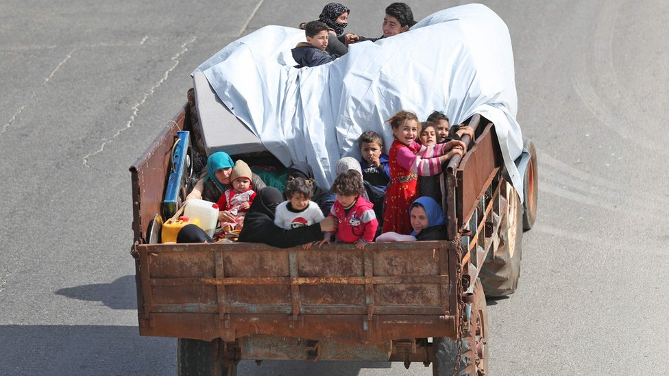 A Syrian family, riding on the back of a lorry, flee southern Idlib province, Syria (6 May 2019)