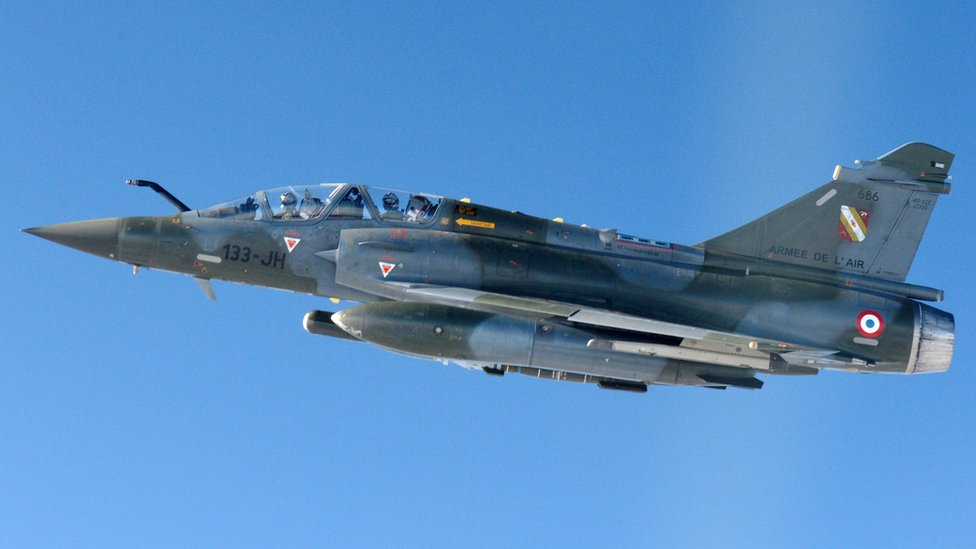 A Mirage 2000-D aircraft with a dark grey camouflage paint job is seen flying in a close-up shot against a bright blue sky
