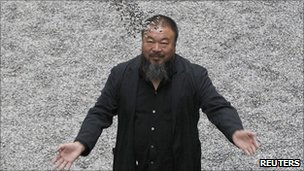 Ai Weiwei poses with his installation Sunflower Seeds at the Tate Modern gallery in London in October 2010