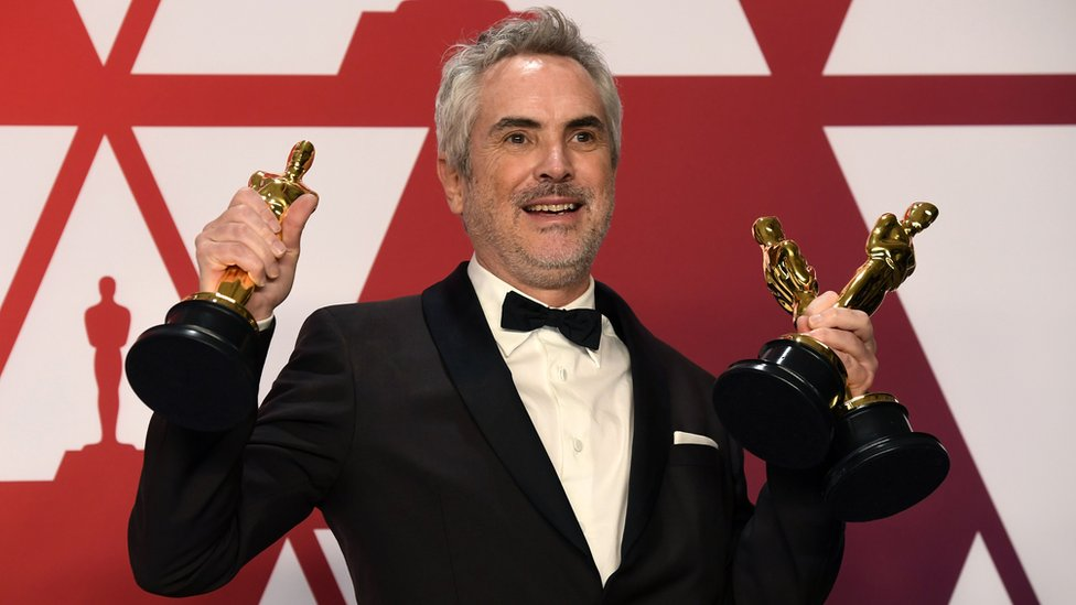 Alfonso Cuaron with Roma's three awards