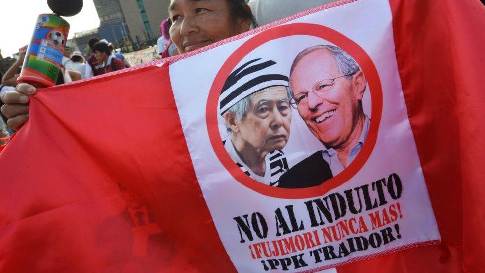 Un manifestante con una bandera peruana que contiene las fotos de Alberto Fujimori y PKK
