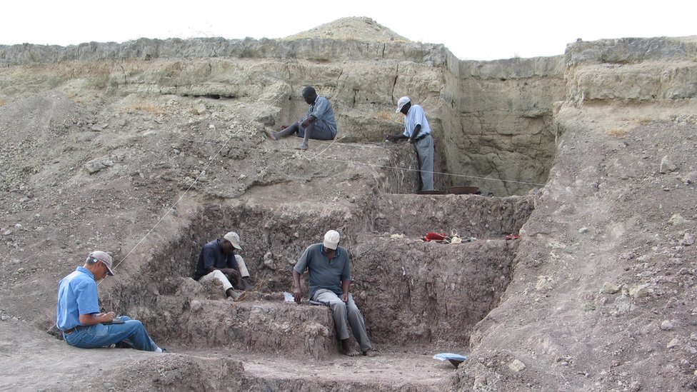 Five men work in a stepped excavation area