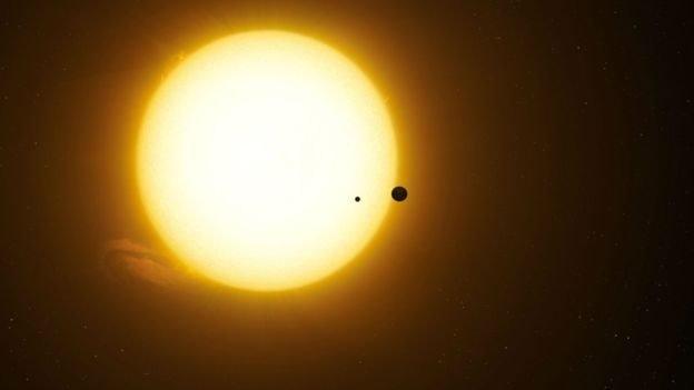 Impresión artística del exoplaneta Kepler-1625b en tránsito por la estrella con la candidata exoluna a cuestas.