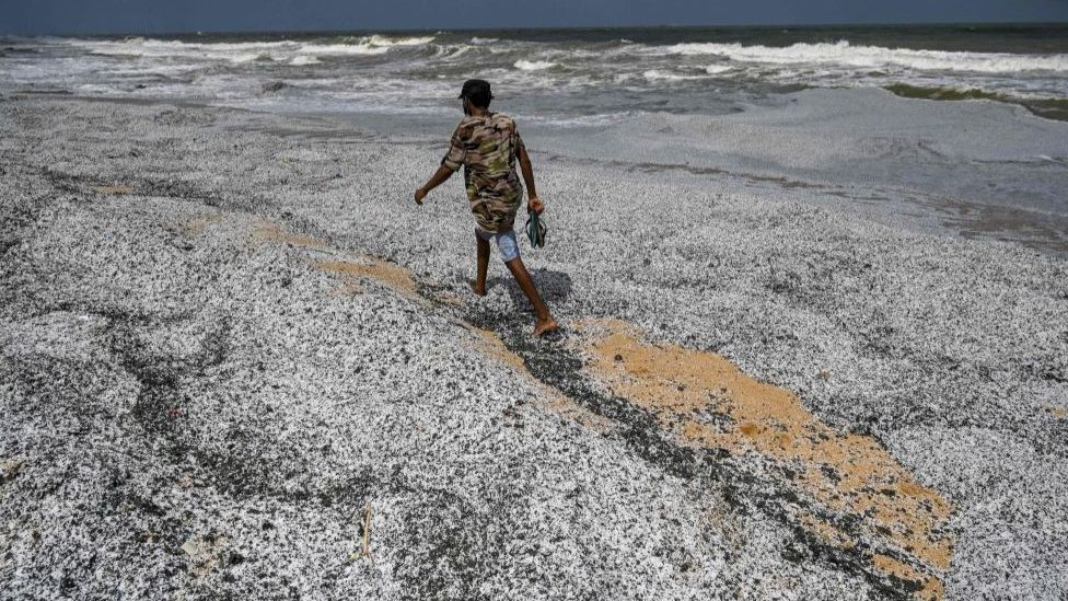 A man walks amid debris washed ashore from the X-Press Pearl on 29 May