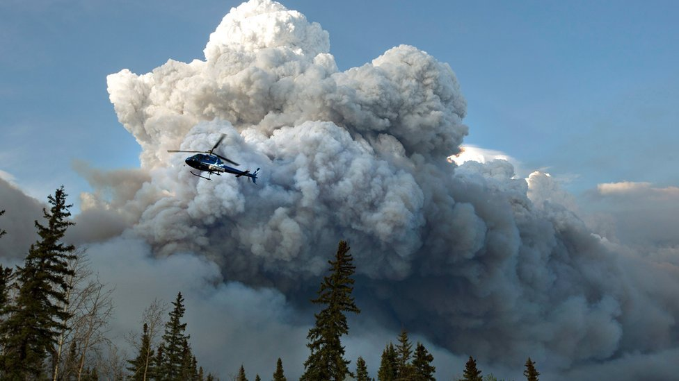 A chopper flies over smoke from wildfires in Alberta, Canada