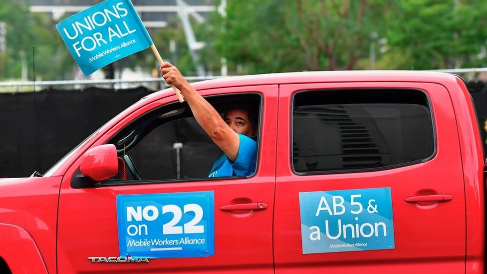 Man in car campaigning against Proposition 22
