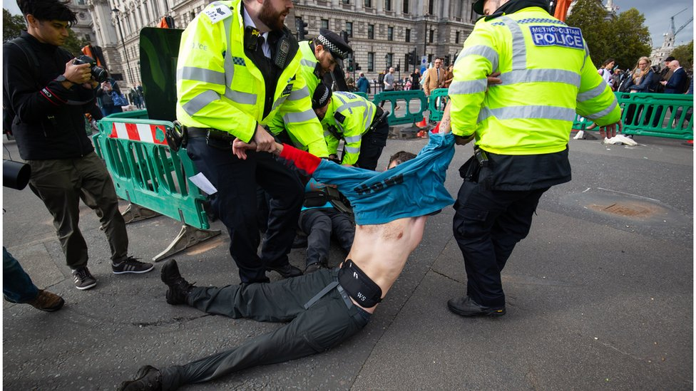 Police officers removing a demonstrator
