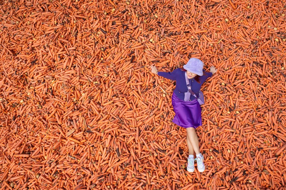A student poses on 29 tonnes of carrots