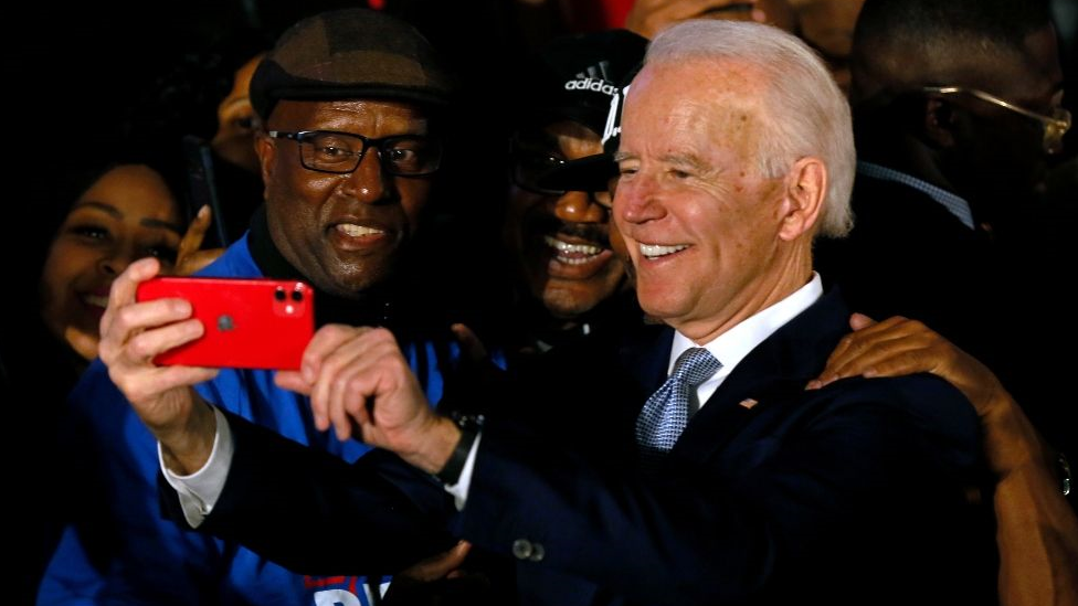 Joe Biden takes a selfie with two voters.