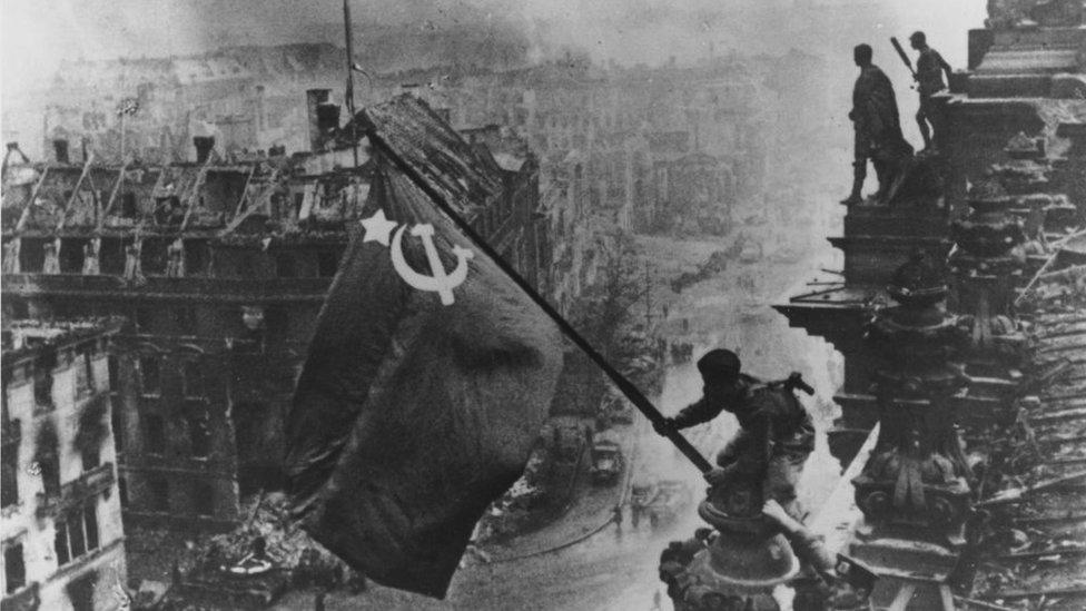 Un soldado ruso eleva la Bandera Roja sobre las ruinas del Reichstag en Berlín.