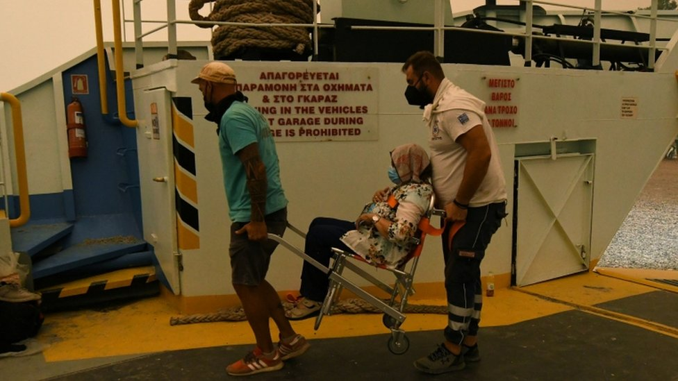 Una mujer es llevada al ferry en Evia.