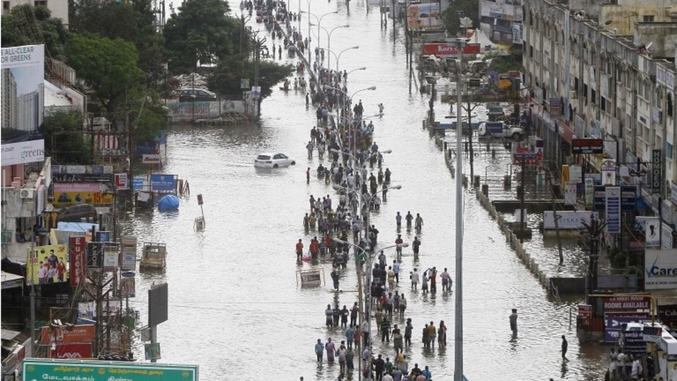 People walk through a flooded street in Chennai, India, Thursday, Dec. 3, 2015