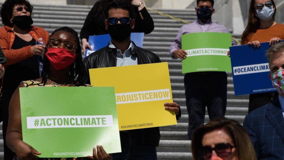 Miembros del partido Demócrata con carteles sobre el cambio climático