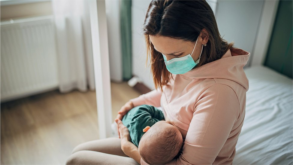 Two people, mother with protective mask breastfeeding her baby son at home