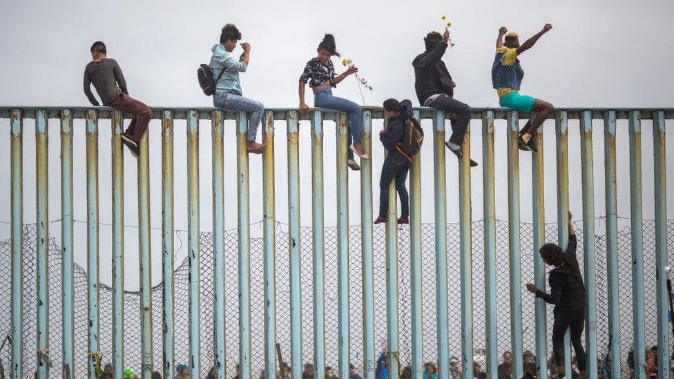 Gente saltando una valla en abril de 2018 en Tijuana, Baja California Norte, México.