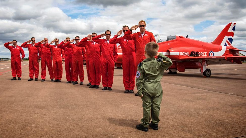 Little boy and Red Arrows crew saluting each other