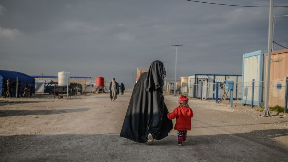 A veiled woman walks with her child at al-Hol camp