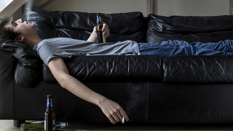Un joven echado en un sofá fumando y bebiendo cerveza
