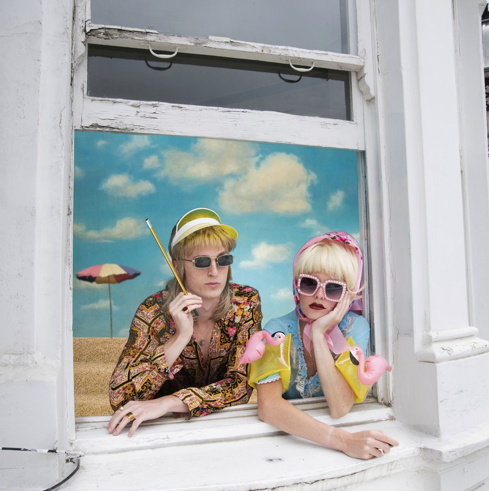 A couple dressed in colourful summer clothes look out of a window on to a beach