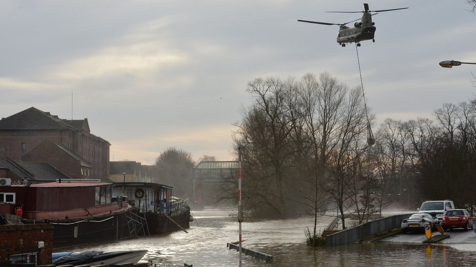 An army chinook helicopter airlifts equipment needed to repair the Foss Barrier on the River Foss