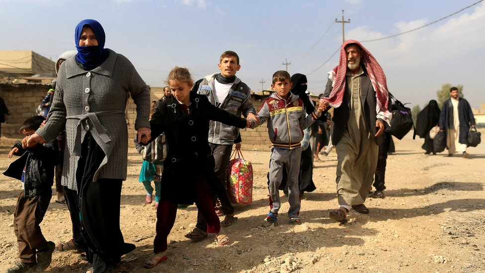 A family fleeing fighting between the Islamic State and Iraqi army in Intisar district of eastern Mosul, make their way to safer territory, Iraq November 8, 2016