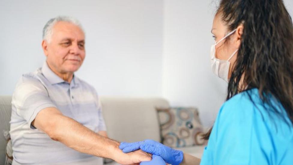 Profissional da saúde atende um indivíduo mais velho