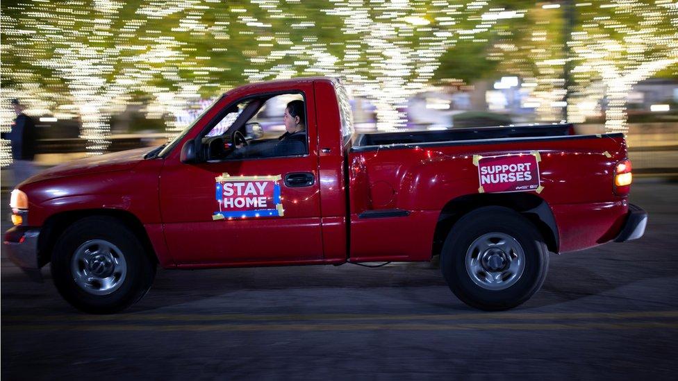"""Una furgoneta roja con carteles de """"quédate en casa"""" y """"apoyo a los enfermeros"""""""