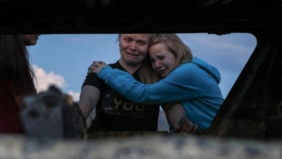 Miembros de la familia LeBarón ante uno de los vehículos quemados tras la emboscada.