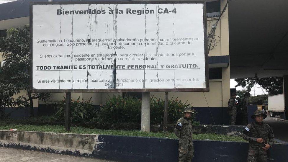 """Militares de pie frente a una valla que dice """"Bienvenidos a la región CA-4""""."""