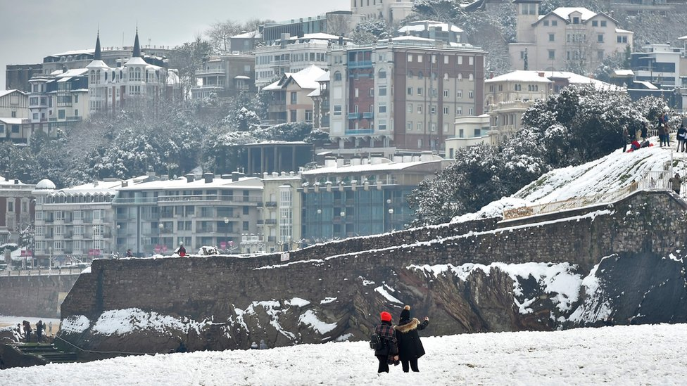 Two people take photos from a white-covered beach with the seaside resort town behind them