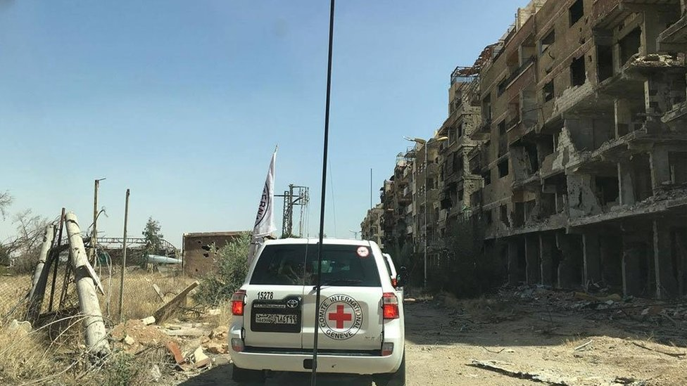 Image by Syrian Red Cross showing aid convoy passing badly-damaged buildings in Darayya, Syria - 1 June 2016