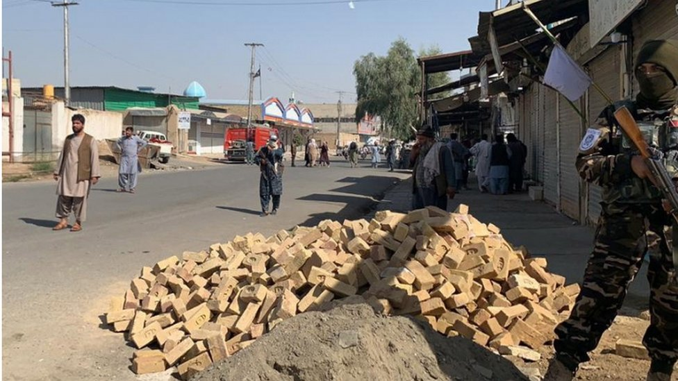 Taliban soldiers guard the road to the mosque