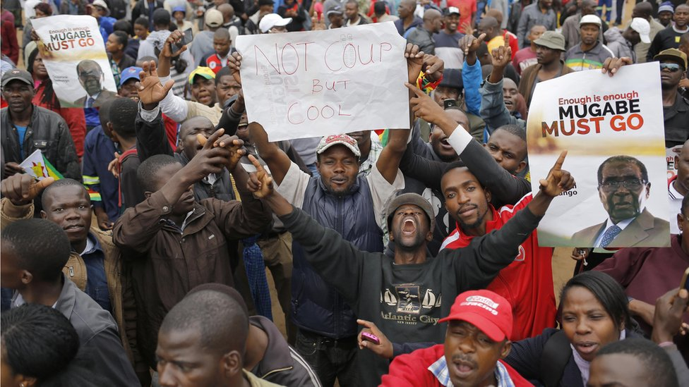 """people holding signs reading """"not coup but cool"""" and """"Mugabe must go"""" in the midst of a sea of people"""