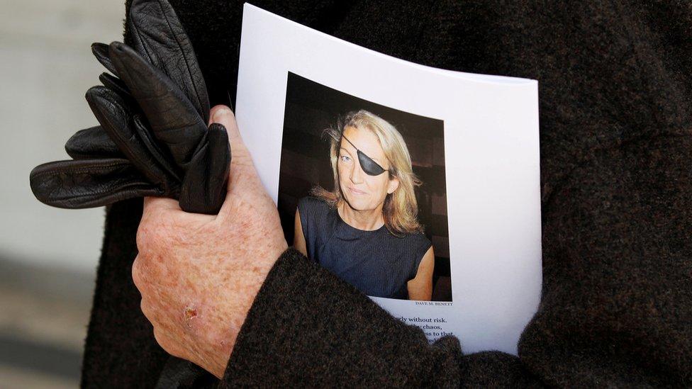 شخص يحمل صورة الصحفية القتيلة ماري كولفين