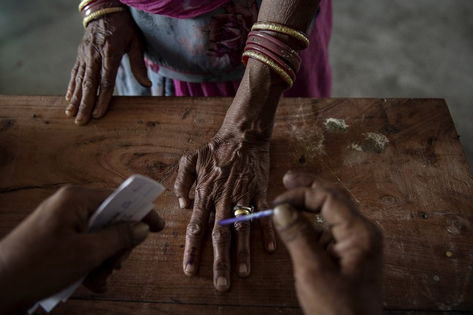 An Indian woman has her finger inked by an election worker before voting in 2014.