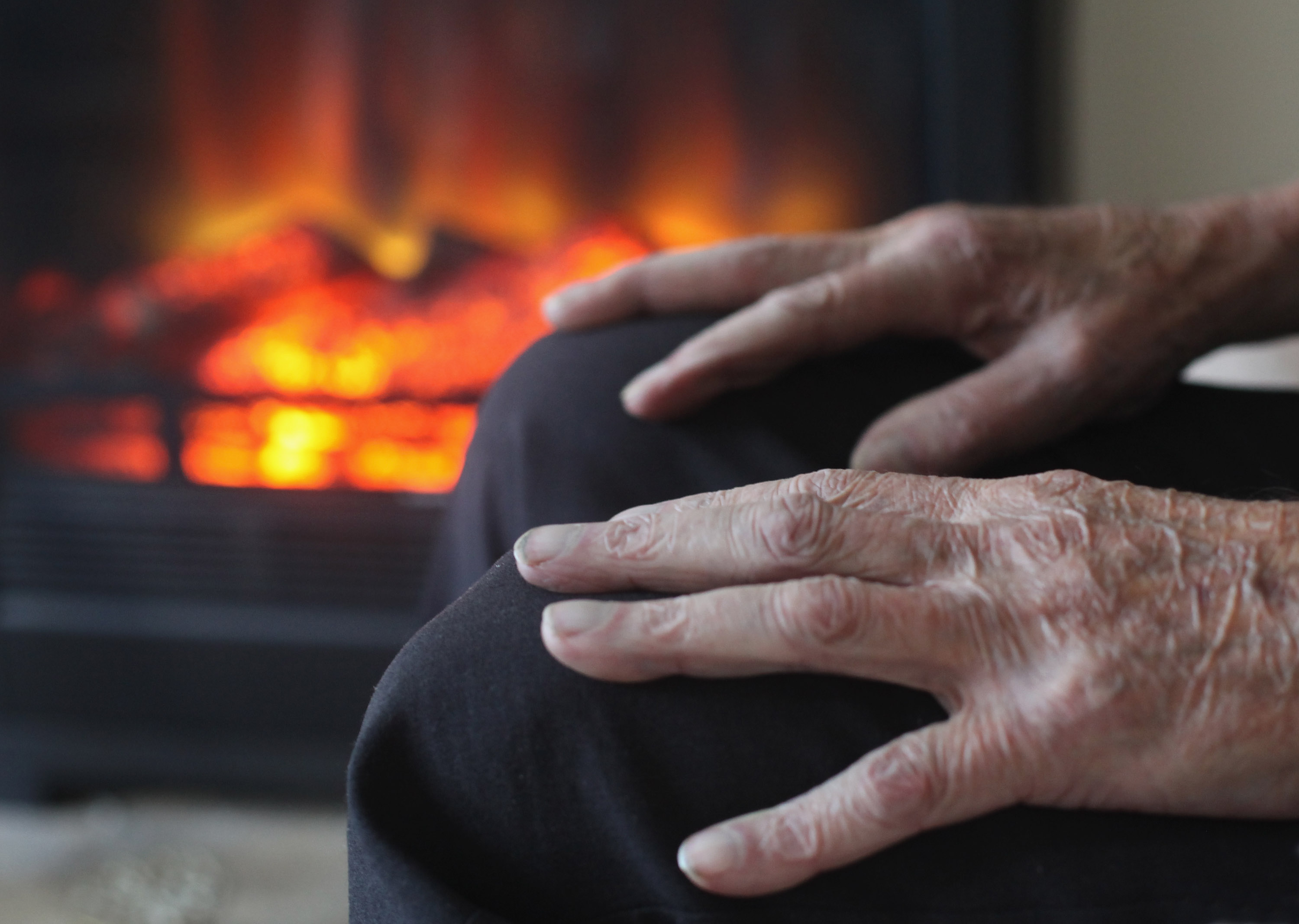 elderly person's hands, sitting by fire